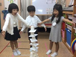 紙コップタワーに驚く3人の子供